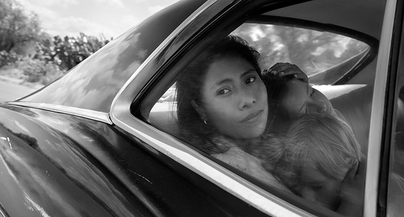 Image from the movie Roma by Alfonso Cuaron showing a woman and children in a car